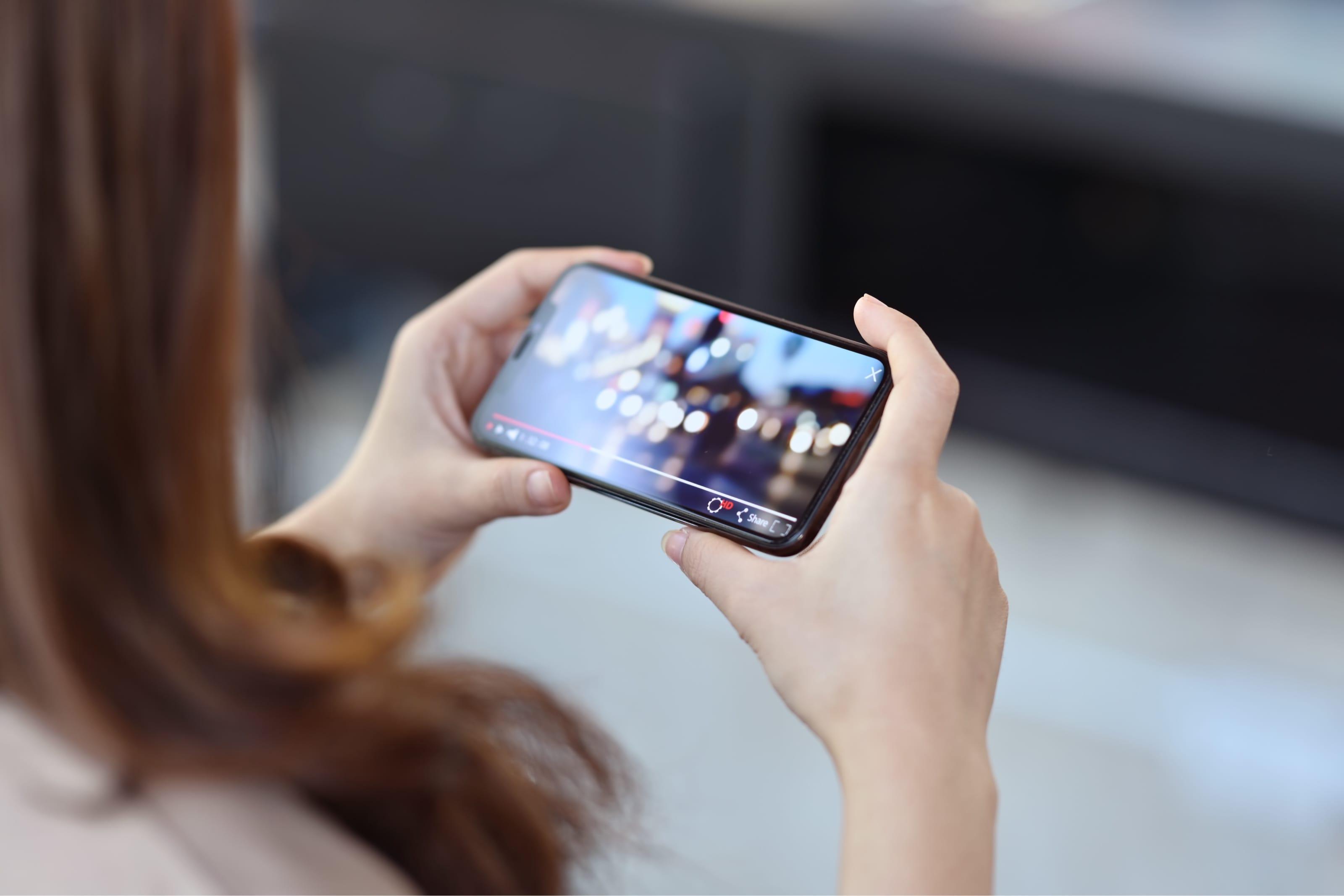 スマートフォンで動画を見る女性