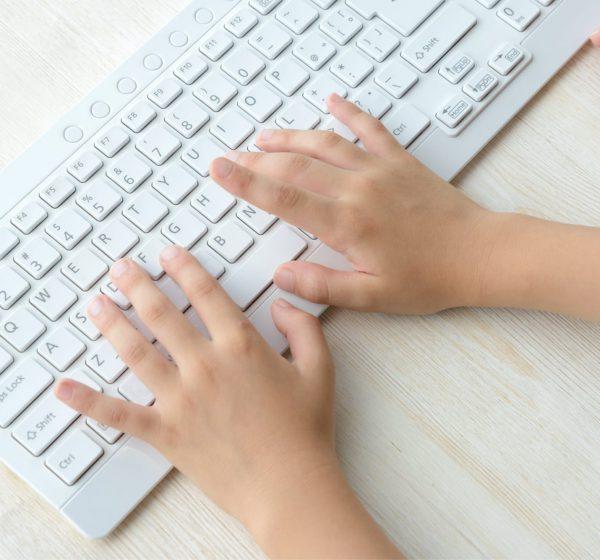 キーボードを操作する子供の手