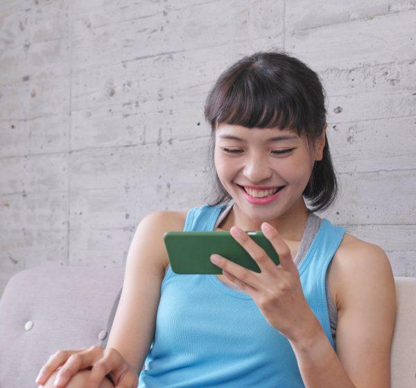 笑顔でスマートフォンを見る女性