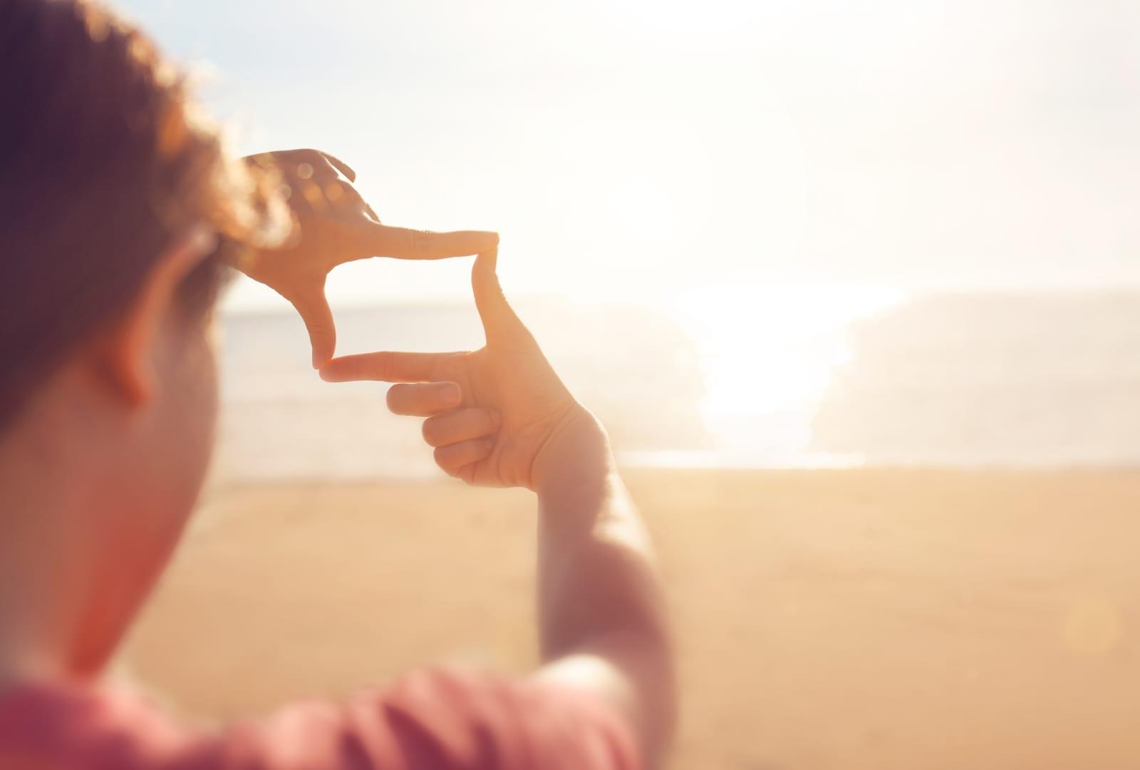 指フレームで海をとらえる女性