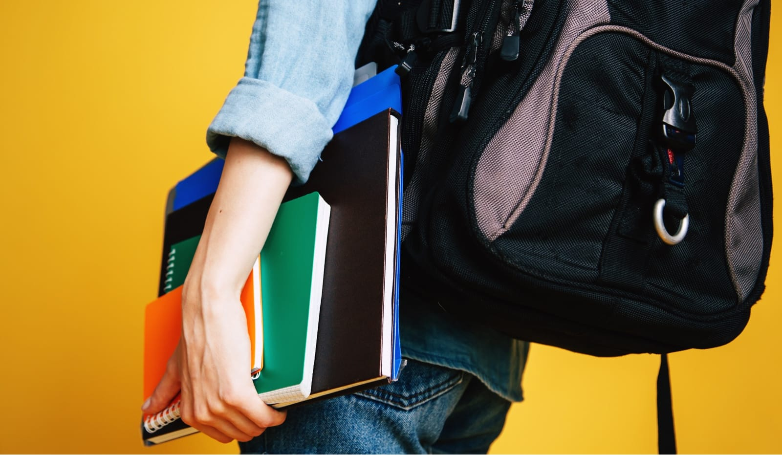 数冊のノートを手に持つリュック姿の人