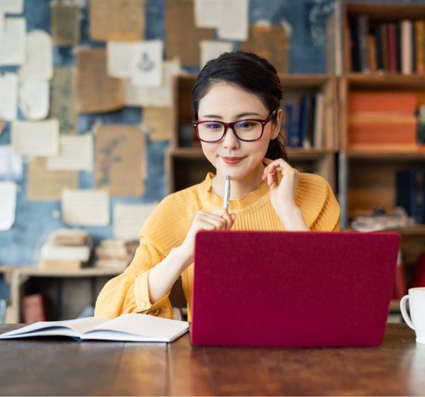 眼鏡をかけた女性がPCを前に勉強する様子