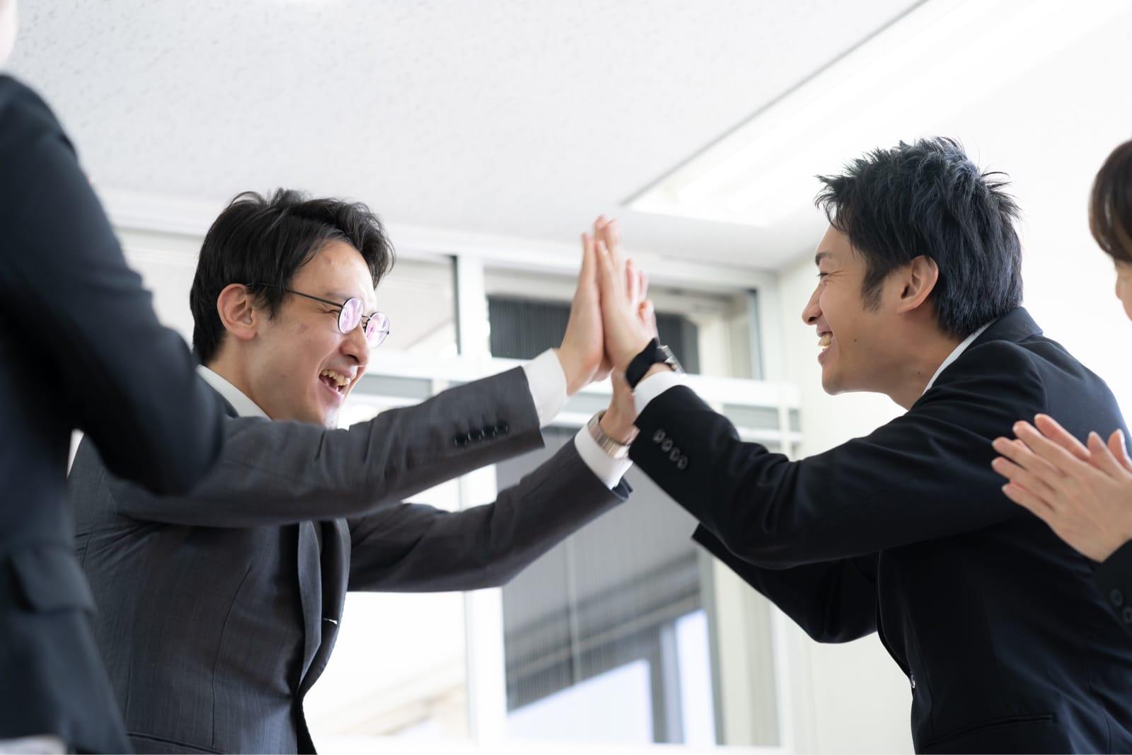 手を合わせて喜ぶビジネスマンたち