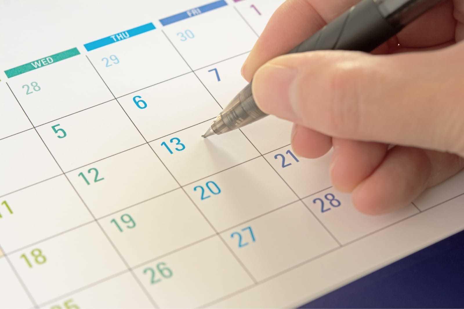 カレンダーにペンで予定を書き込む様子