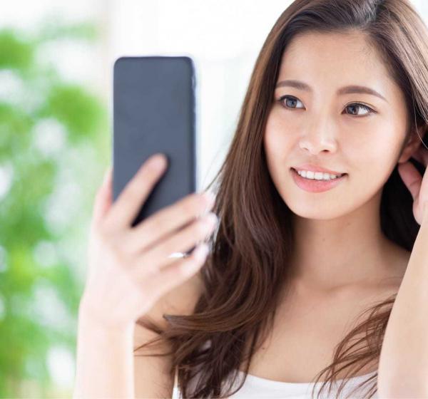 スマートフォンで自分を撮影する女性