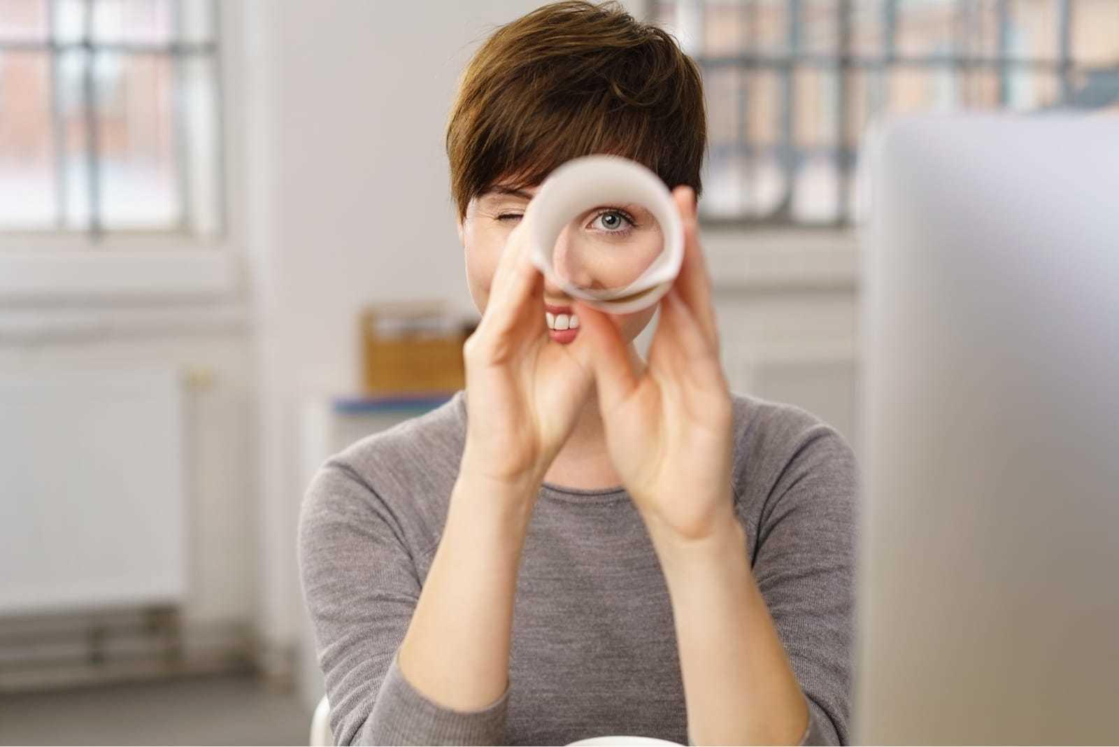 紙で作った輪をのぞく女性