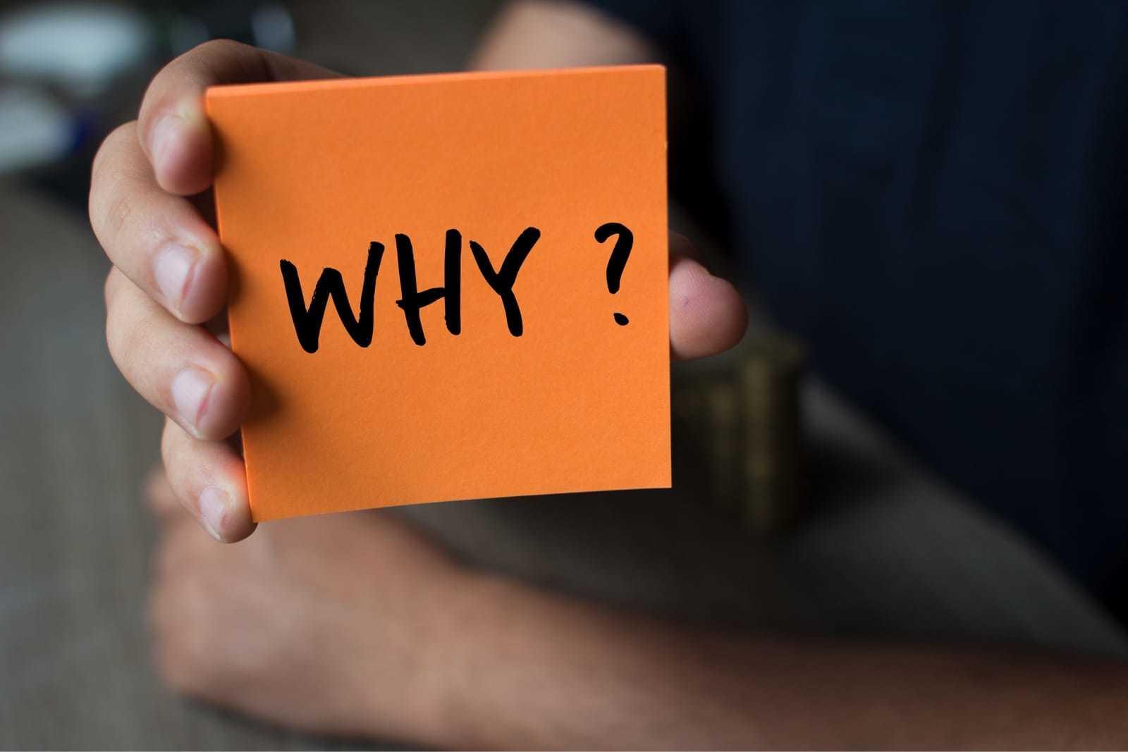 「Why」と書かれた紙を手にする女性