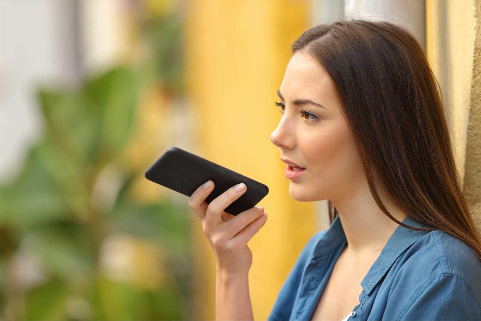 スマートフォンに話しかける女性