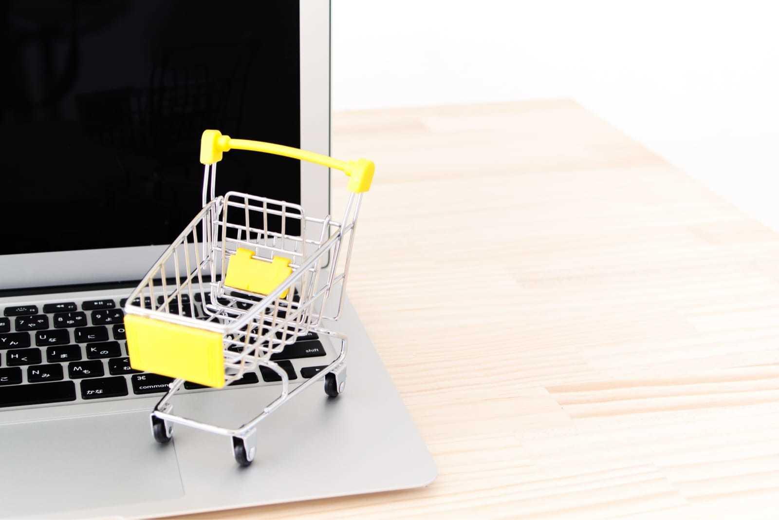 ノートパソコンに置かれた小さなショッピングカート