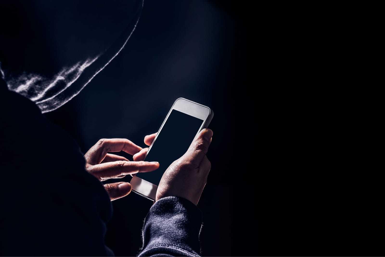 スマートフォンでハッキングするフードを被った男性