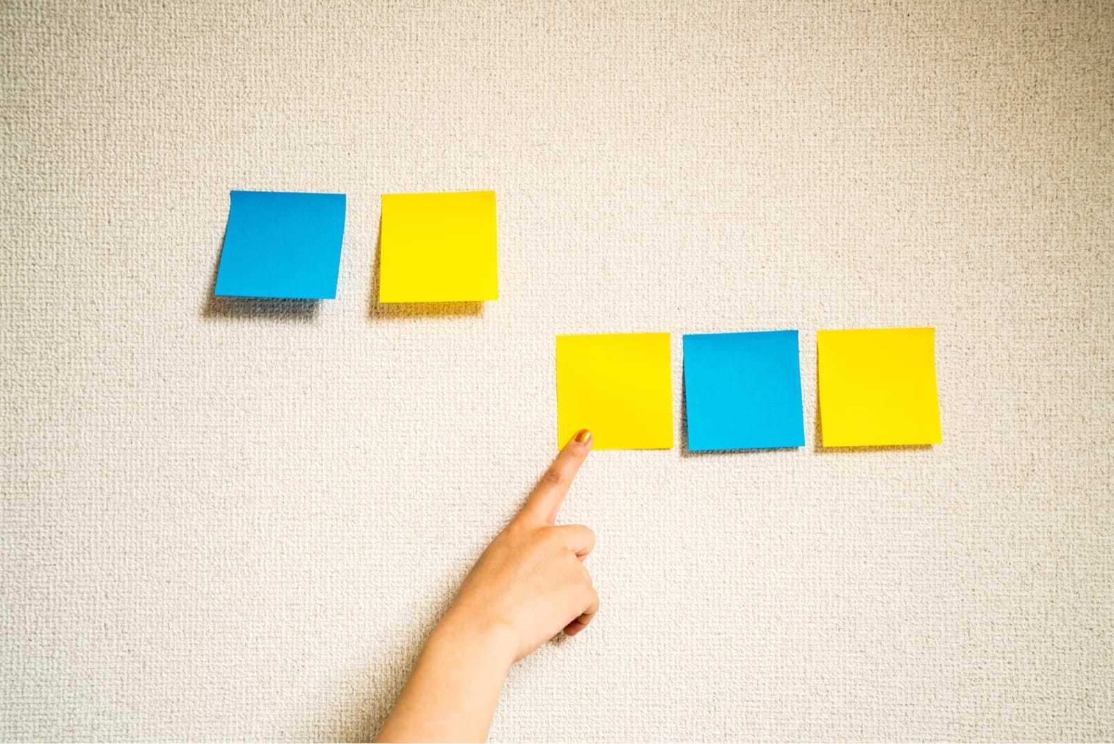 黄色い付箋を指差す女性の手