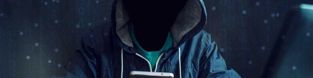 スマートフォンをハッキングしようとするフードを被った男性