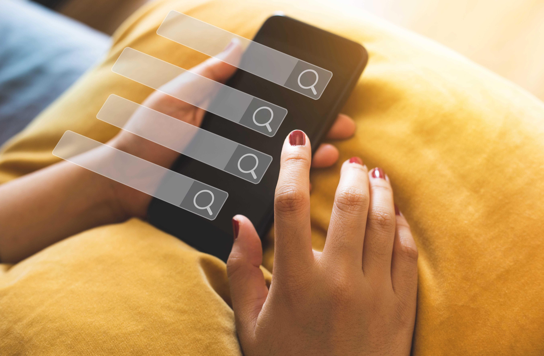 スマートフォンで検索する女性の手