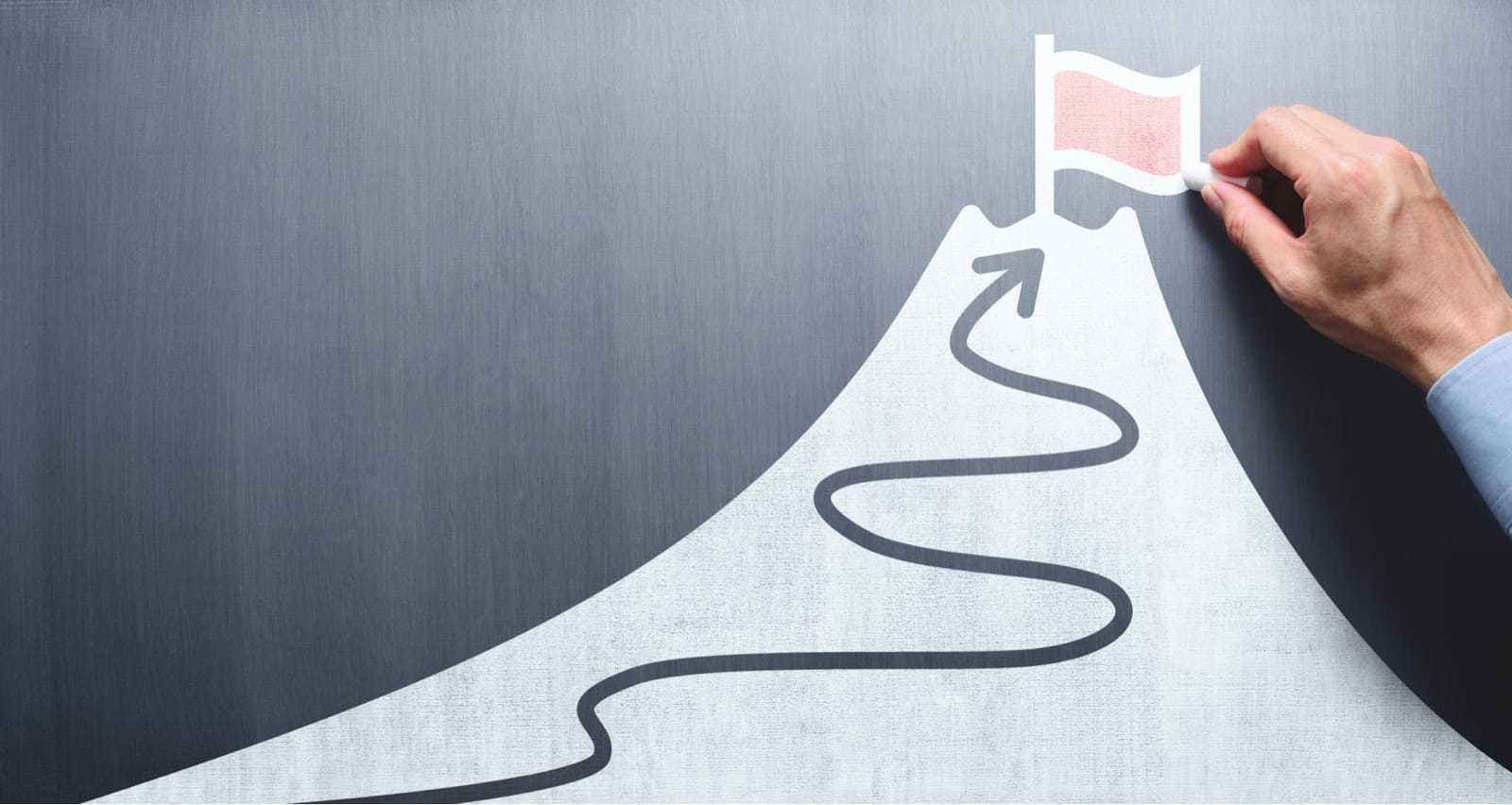 黒板に旗と山を描くビジネスマン