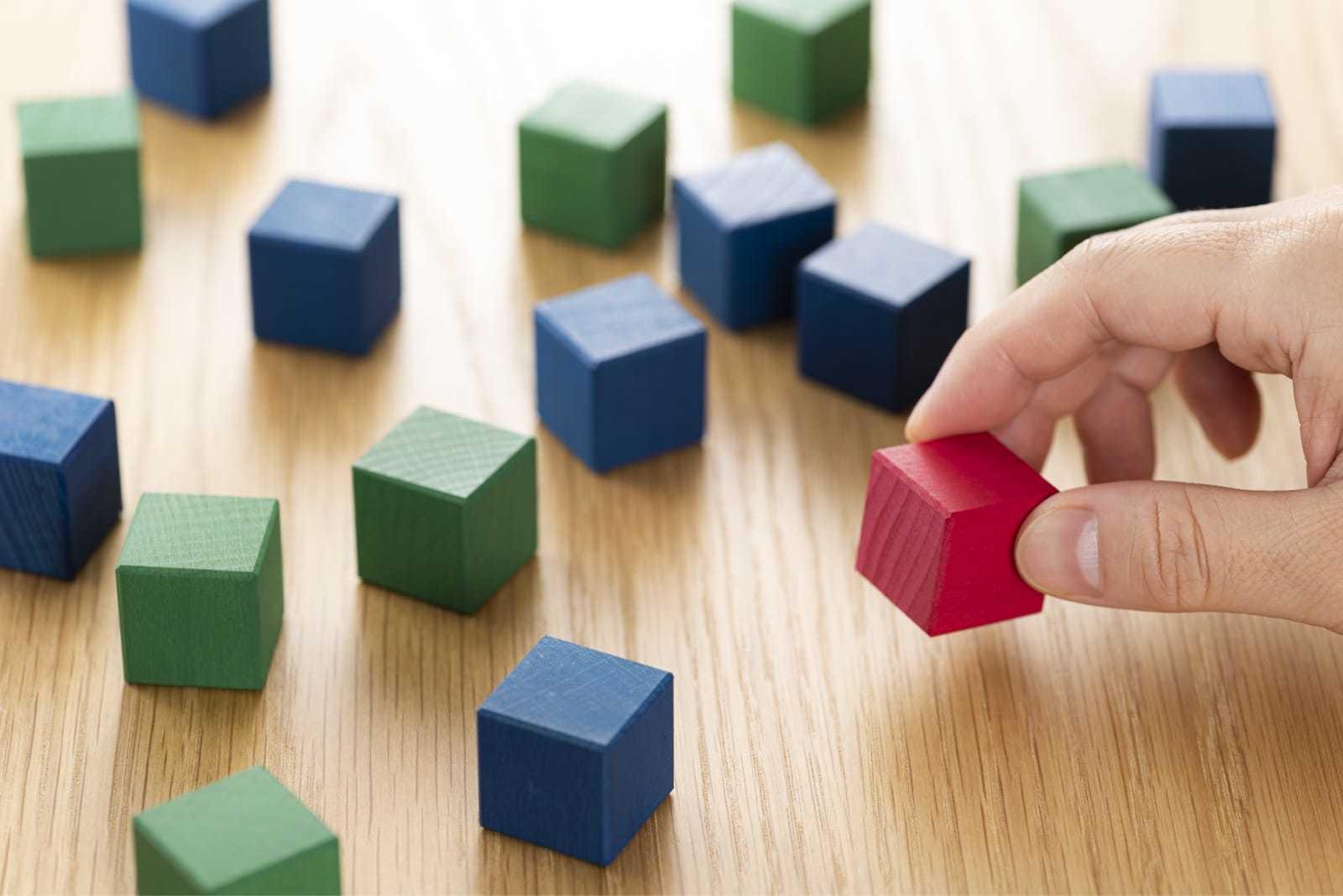 複数色のブロックの中から、一つだけの赤いブロックを選ぶ様子