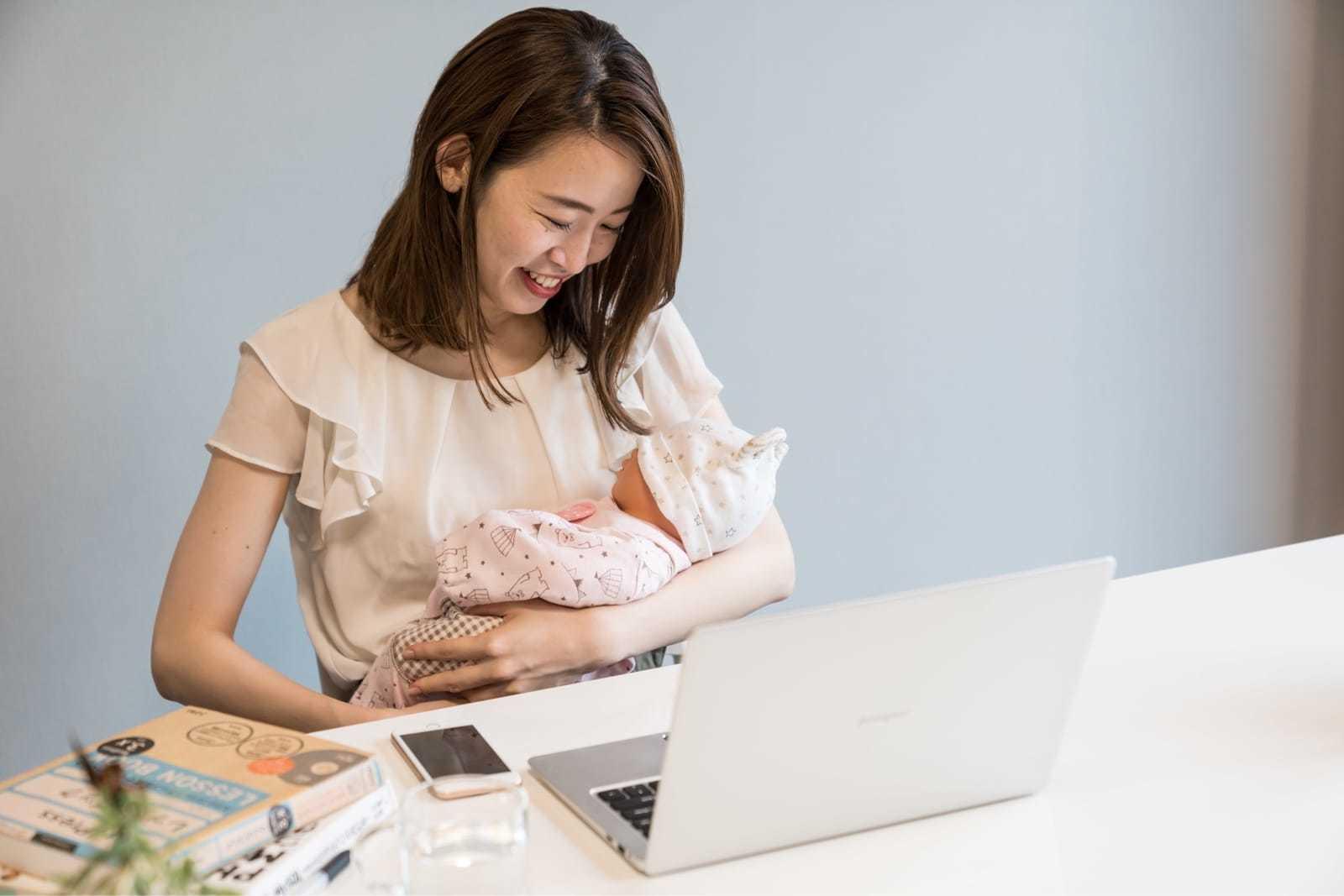 子供を抱きながらパソコンの前に座る女性