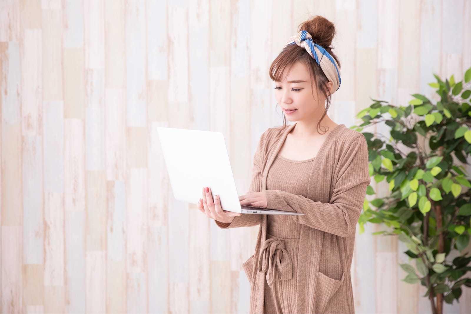 ルームウェアでノートパソコンを操作する女性