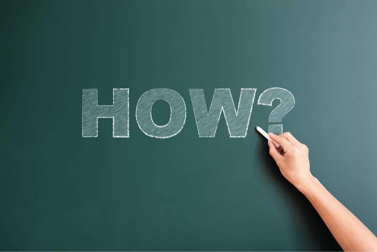 「HOW」と黒板に書く手