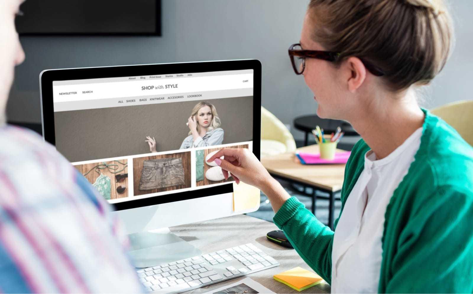 パソコンに表示されたホームページを指す女性
