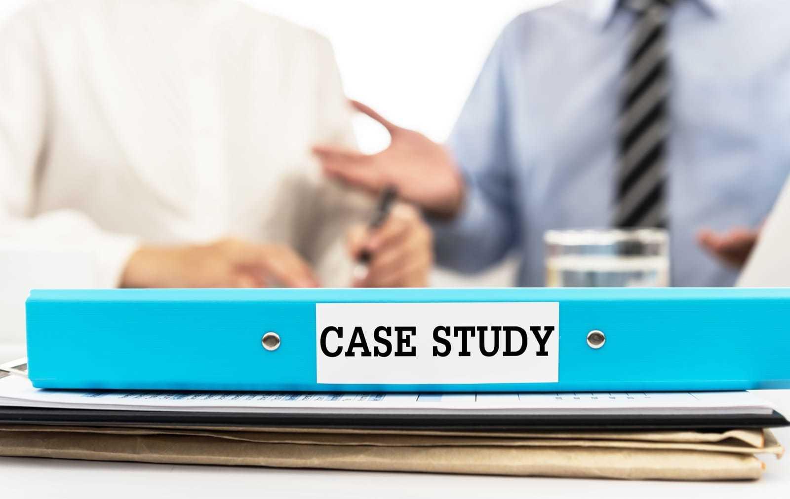「case study」と書かれたファイルを前に話し合う男性と女性