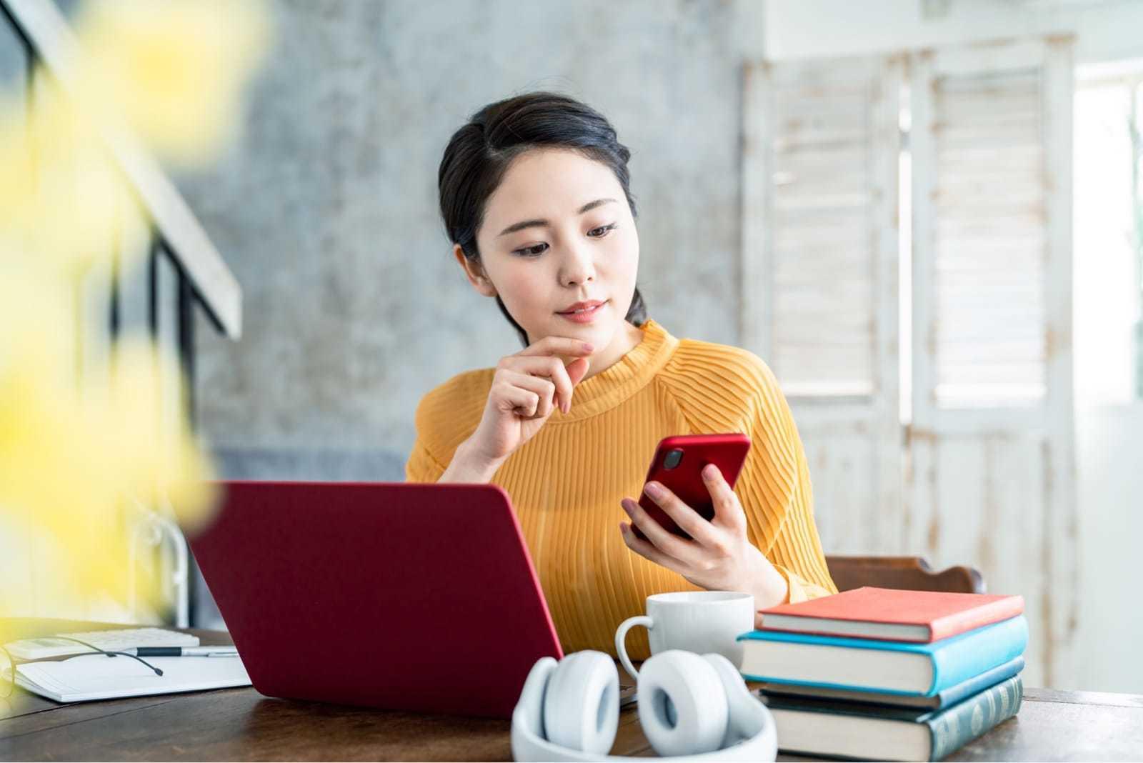 ノートパソコンを広げながらスマートフォンを見る女性