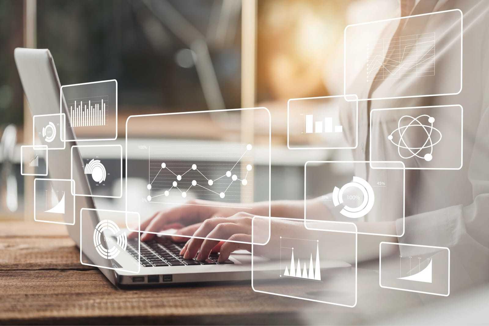 ノートパソコンで仕事をする女性と、その上に浮かび上がるデジタルデータのイメージ