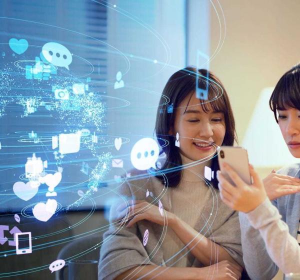 女性二人がスマートフォン画面を見つめる様子