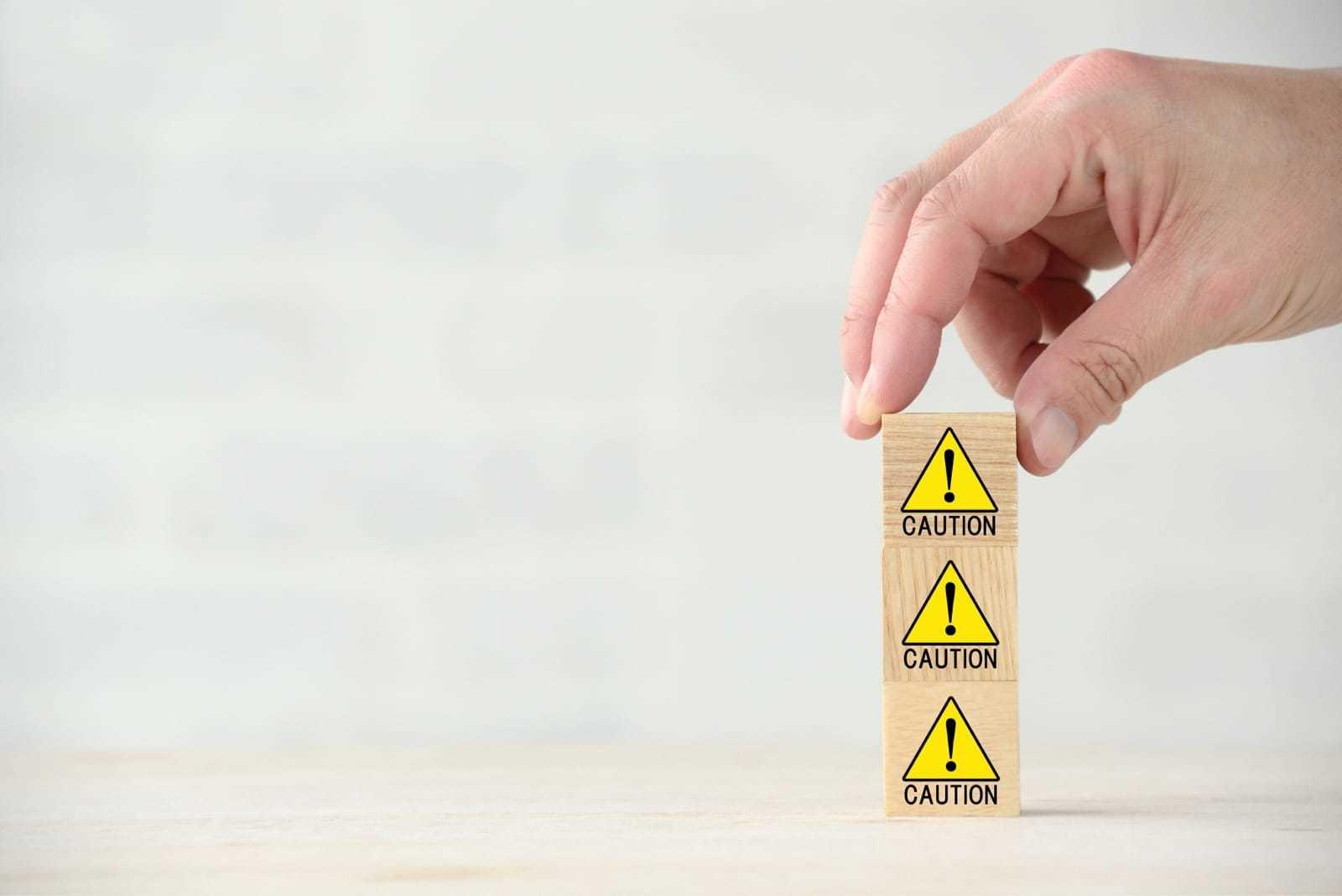 「CAUTION」ブロックが3つ積み上げられる様子