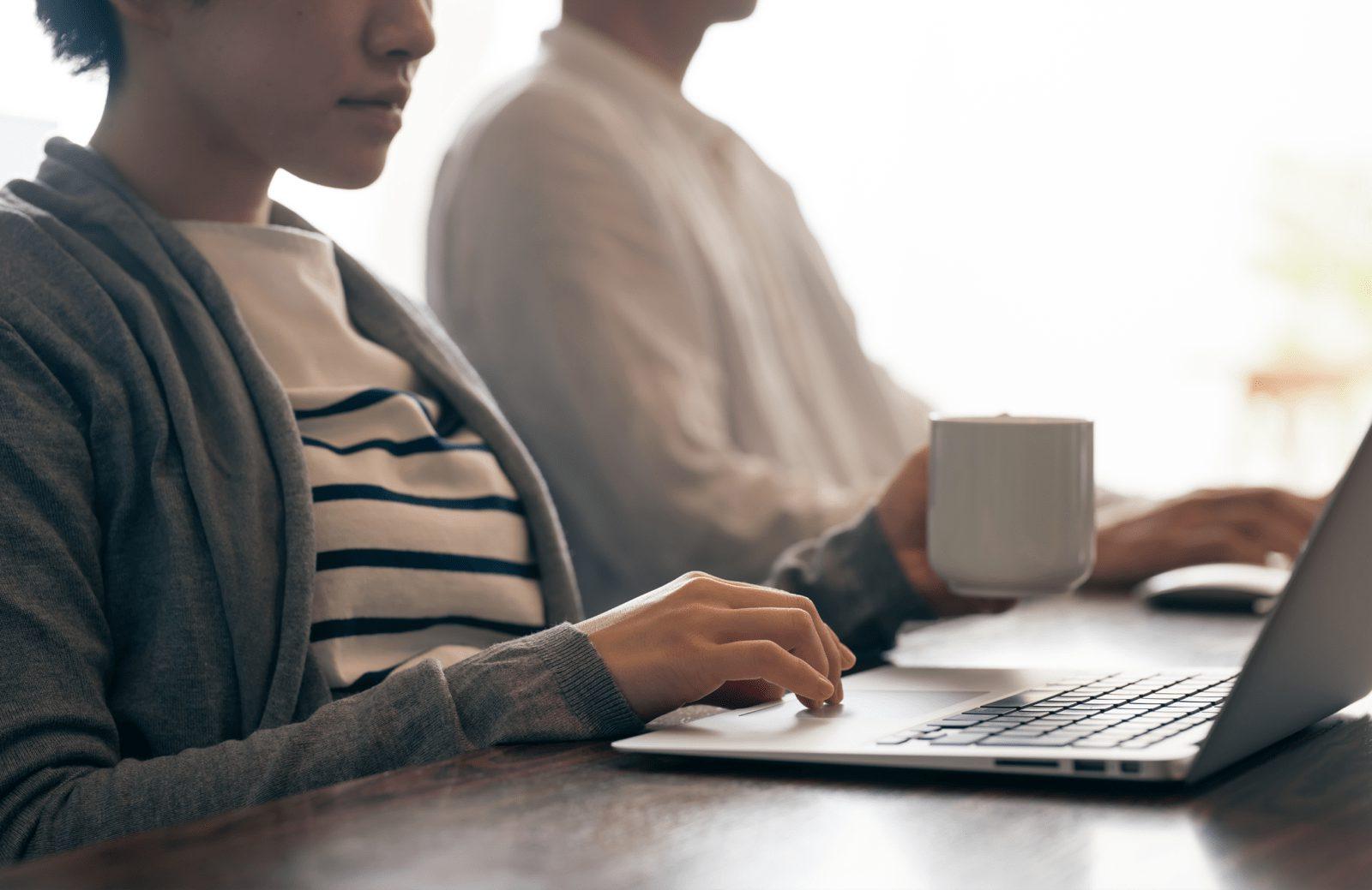 コーヒーを飲みながら仕事をする男性