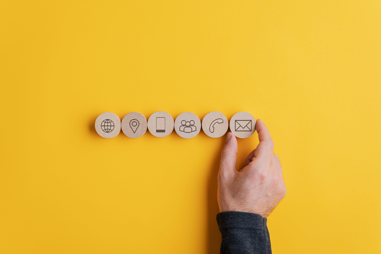 様々なアイコンが書かれた丸いブロックを並べる男性の手