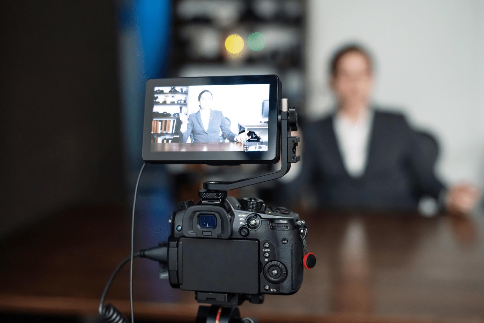 スーツ姿で動画を撮影する人