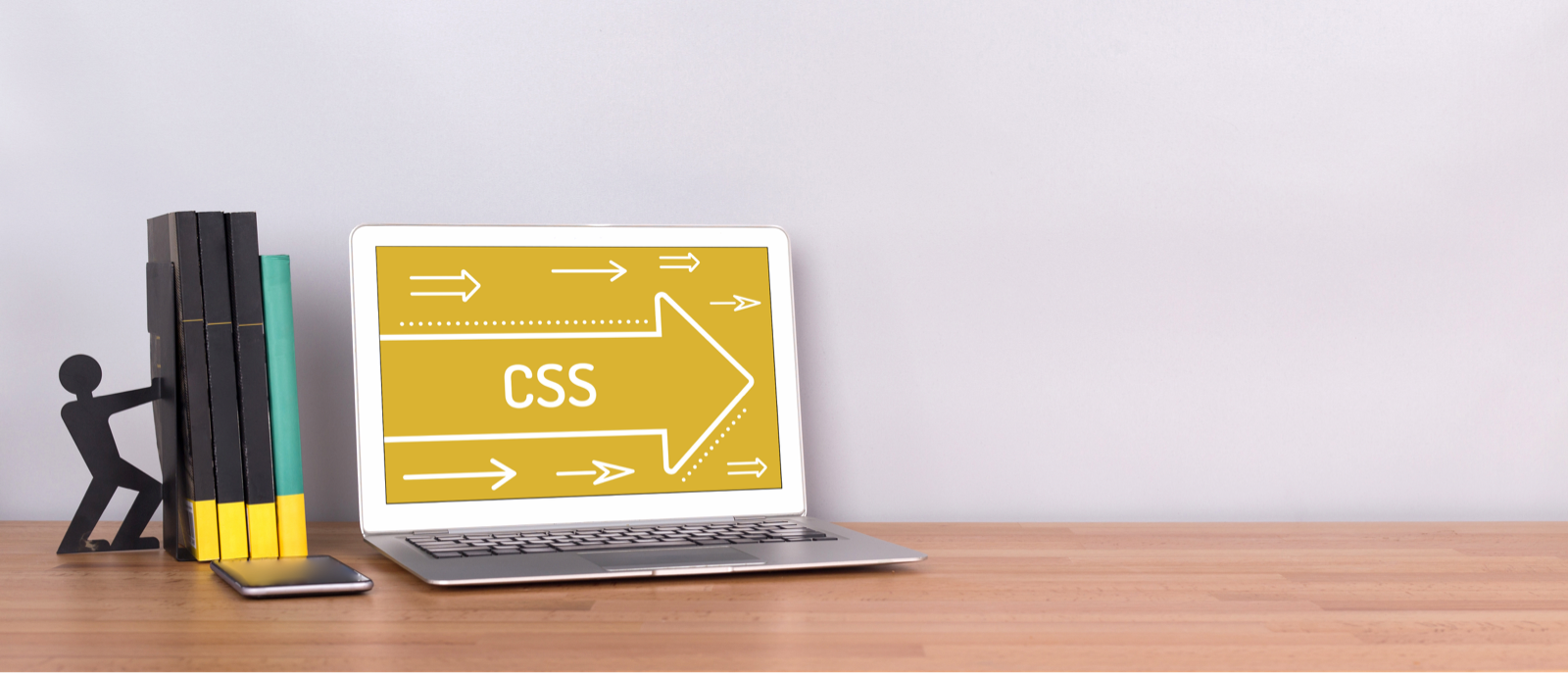 「CSS」と表示されているノートパソコンと、ブックエンドの本