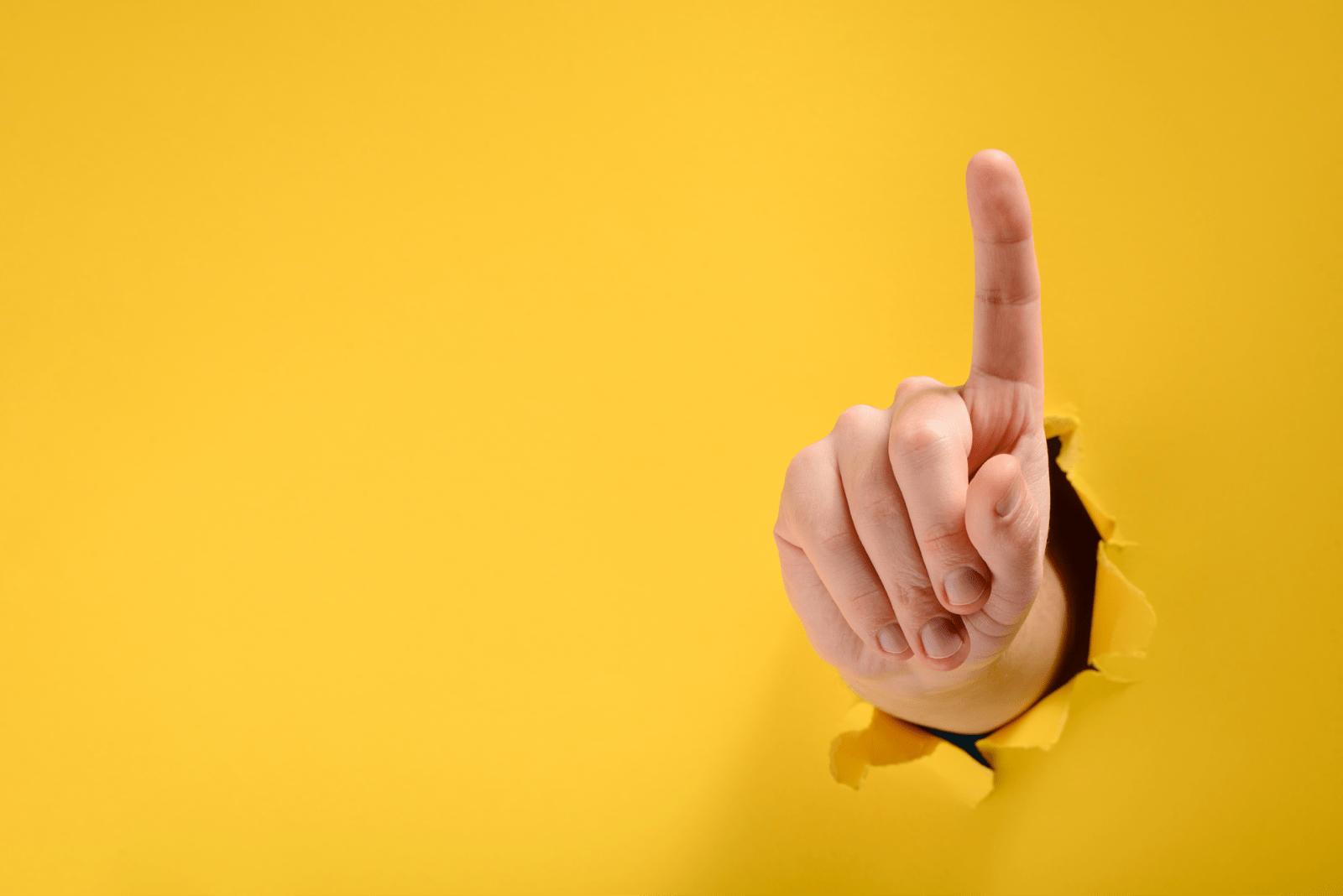黄色い紙を突き破って人差し指を立てる