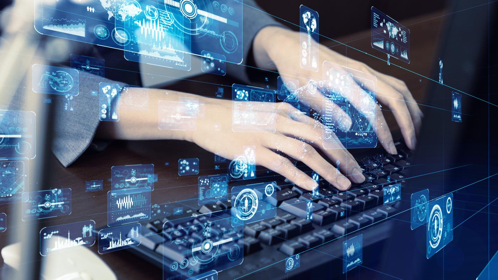 パソコンを操作する人と、その上に浮かび上がる図形などのイメージ