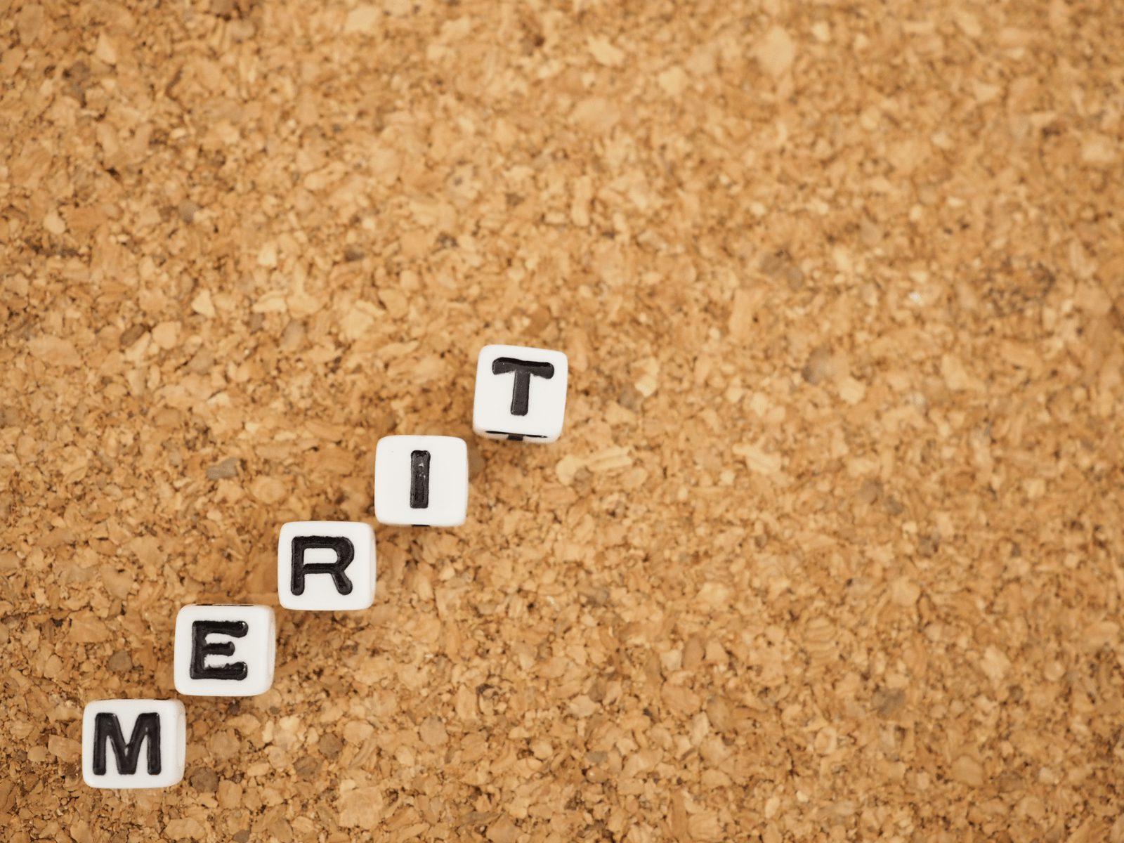 コルクボードに置かれた、メリットという単語の四角いキューブ