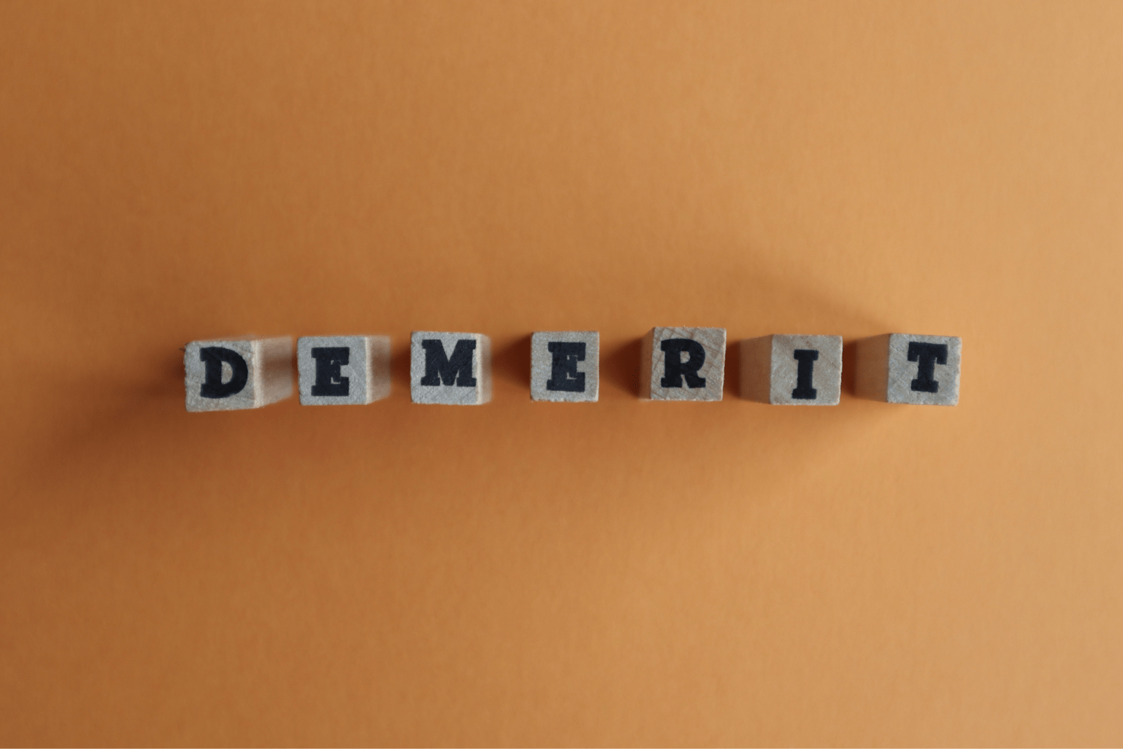 「DEMERIT」と印字された木のブロック