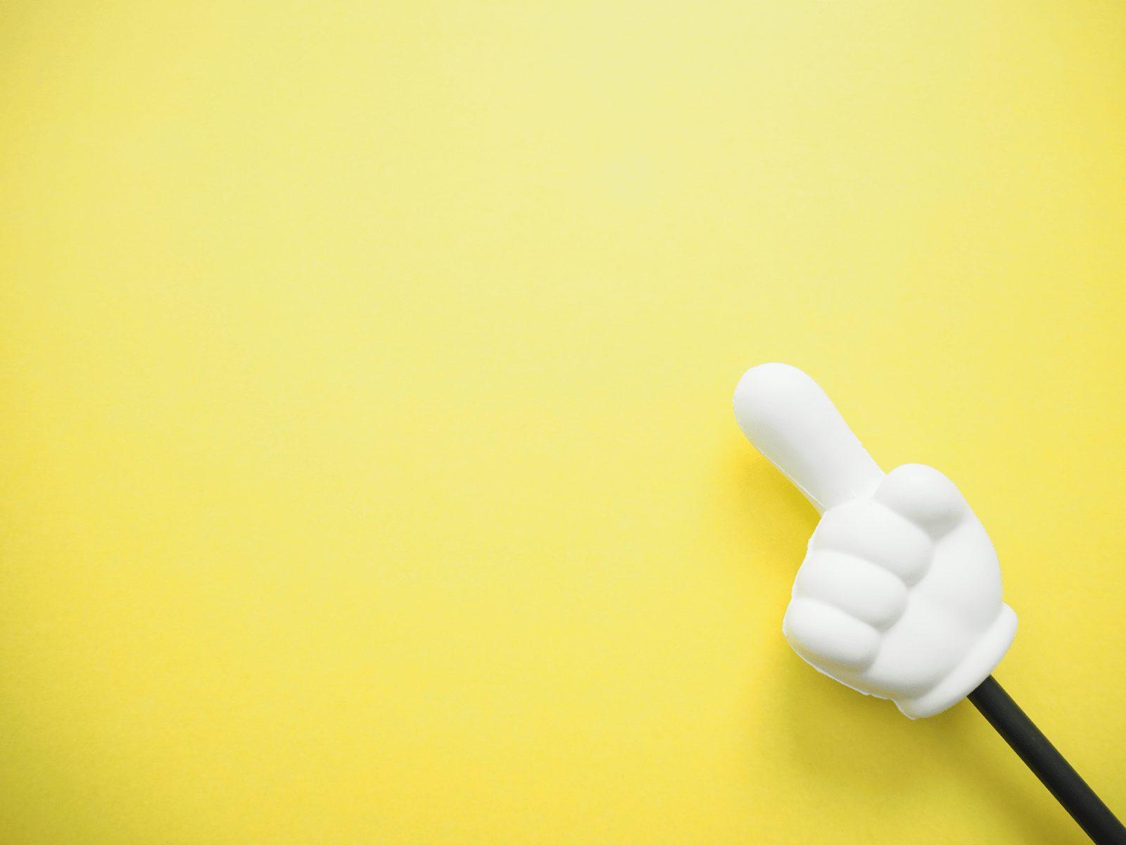 黄色の背景に指差し棒