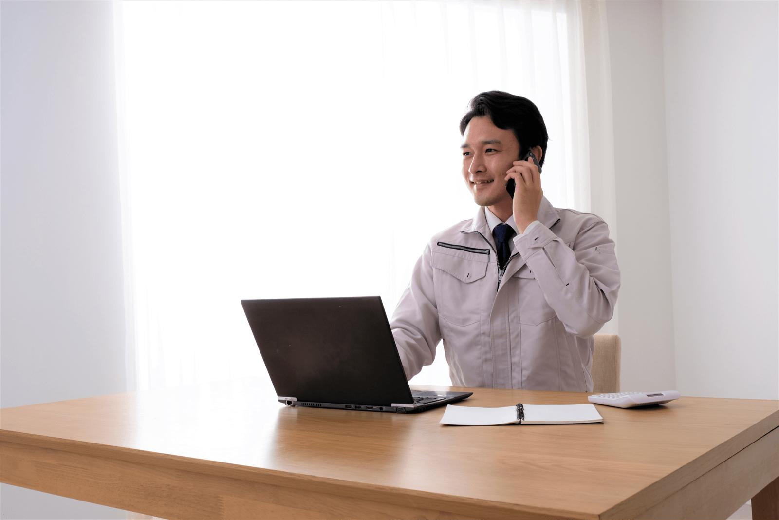 作業着を着た男性が、パソコンの前で電話をする様子