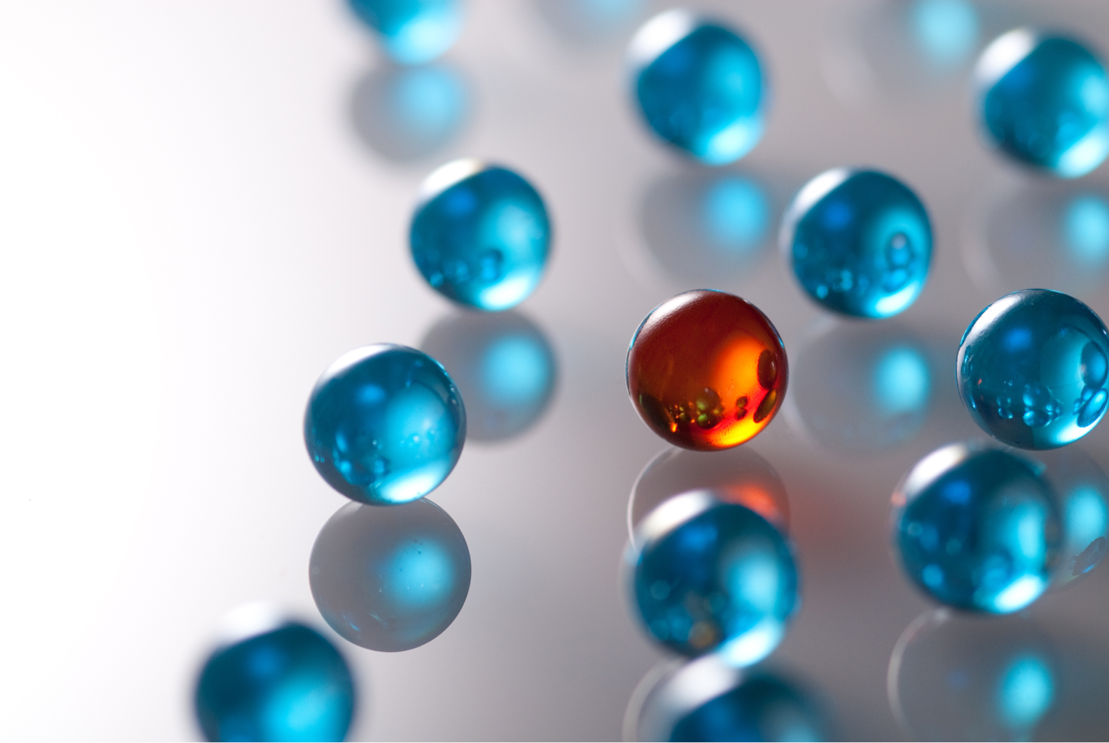 複数の青いビー玉の中に、一つの赤いビー玉