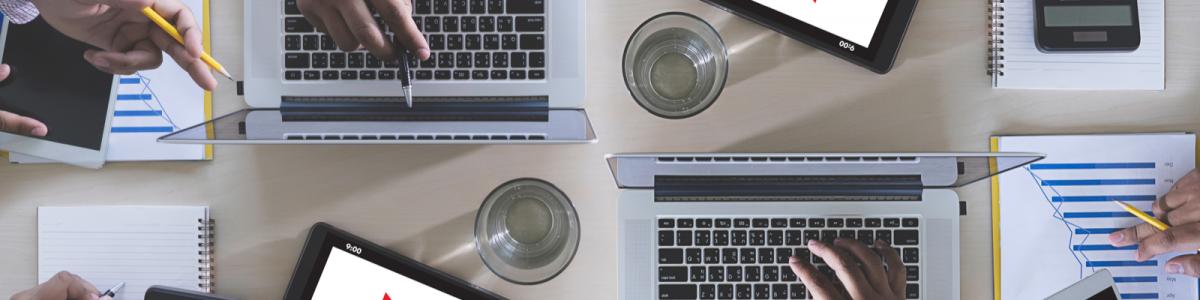 複数のビジネスマンが、ノートパソコンとタブレットで仕事をしている様子