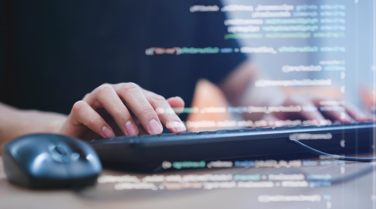 パソコンを操作する女性と、プログラミング言語が浮かび上がる様子
