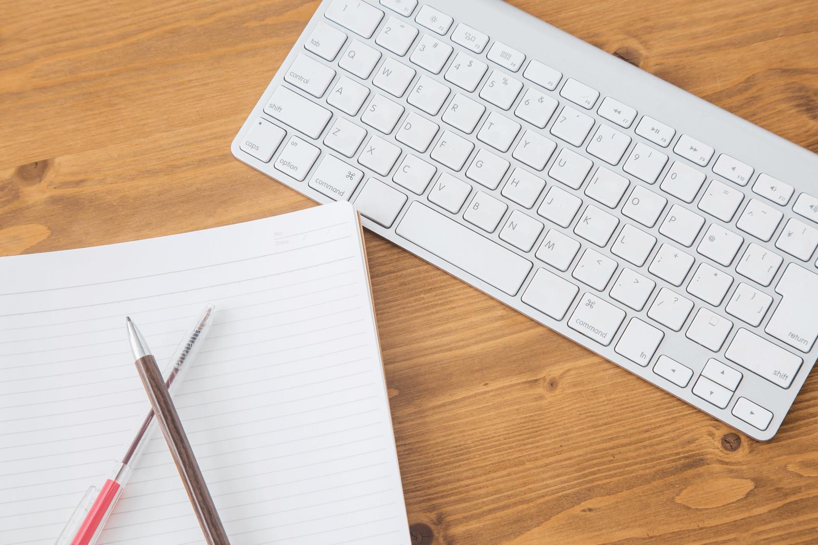 テーブルに置かれた筆記用具とパソコンのキーボード