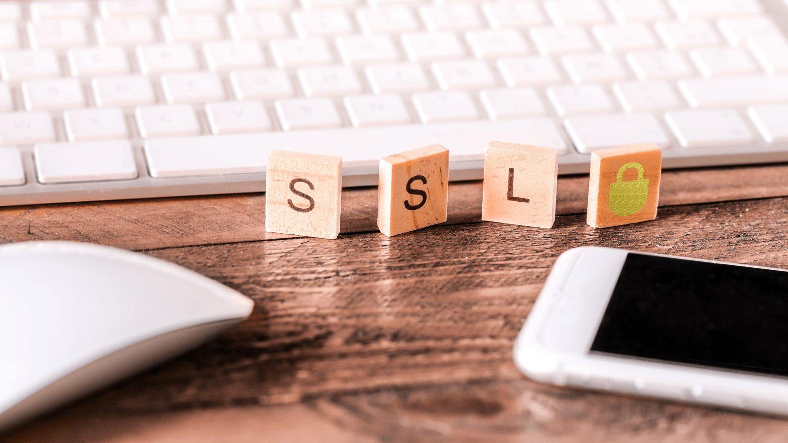 「SSL」と書かれた木のブロックがパソコンのキーボードの前に置かれている