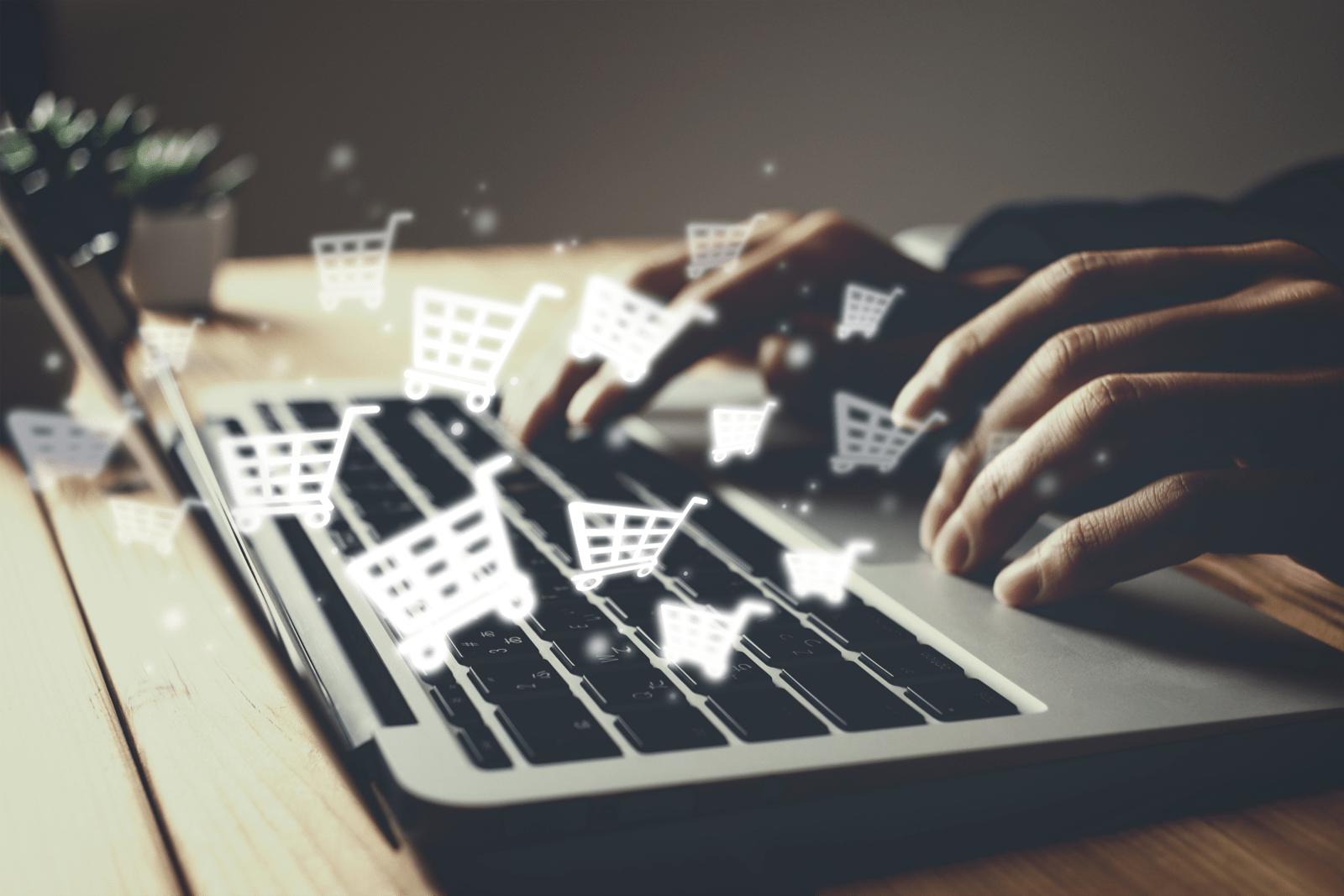 ノートパソコンのキーボードに、複数のショッピングカートのアイコンが浮かぶ、ネットショッピングのイメージ図
