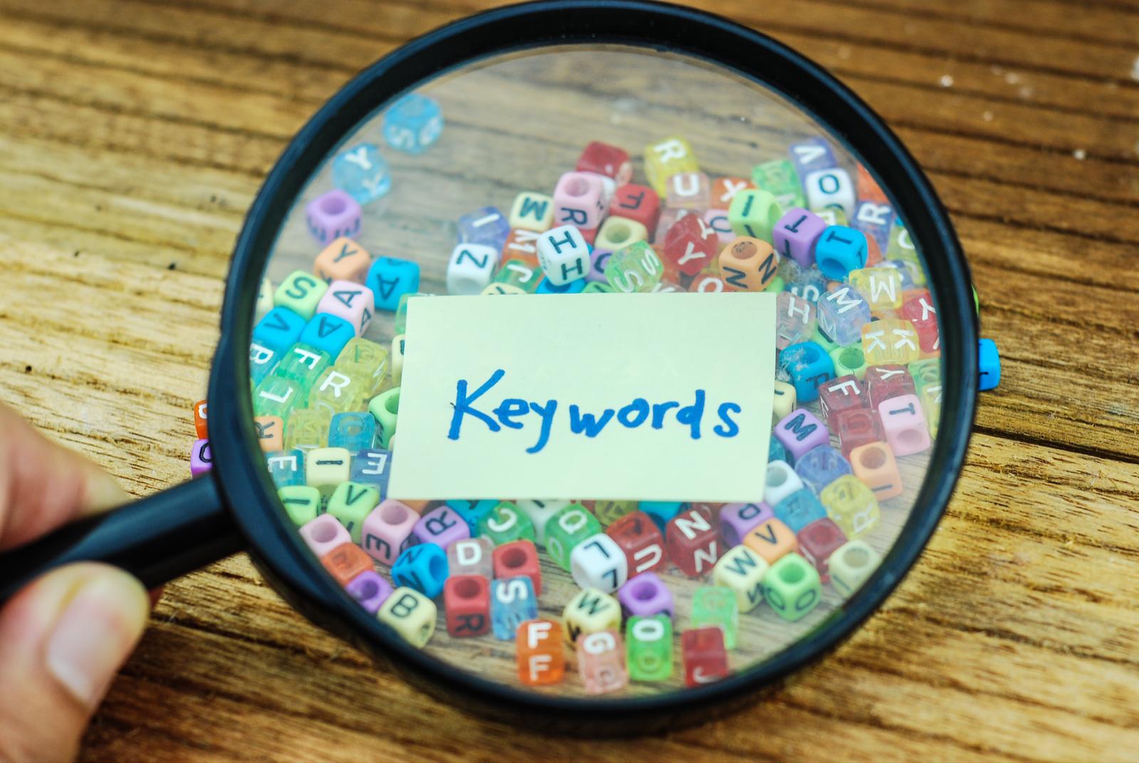 小さなブロックと、付箋に書かれた「Keywords」の文字。それを拡大する虫眼鏡。