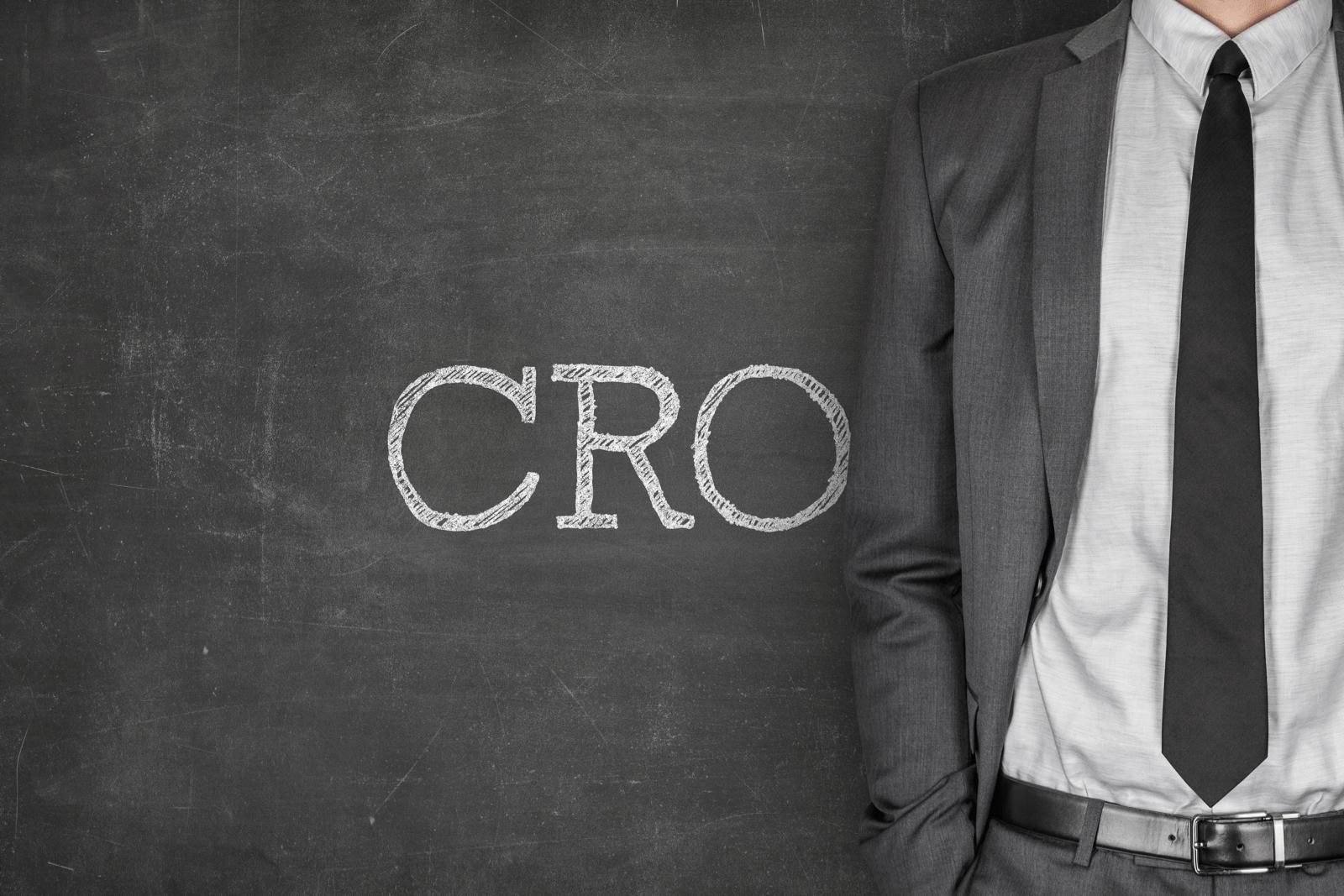 黒板に書かれたCROの文字と、横に立つビジネスマン
