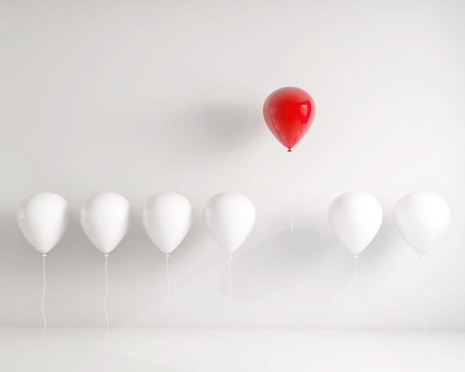 複数の白い風船と、一つの赤い風船