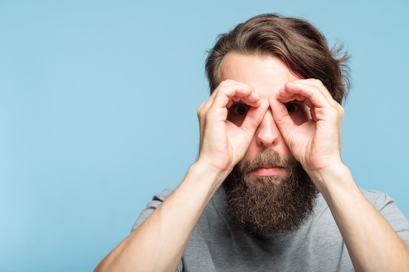 両手をメガネのように丸めて目に当てる男性
