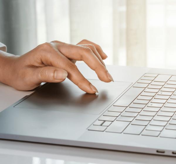 ノートPCをタッチする女性の手元